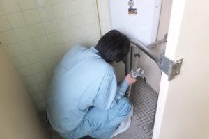 男子トイレタンク修理中