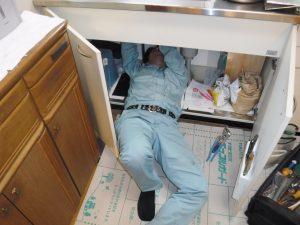 収納扉の中から水栓取り換え作業中