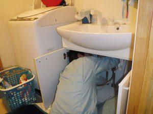 洗面台下での水漏れ修理作業中
