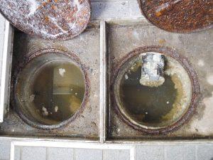 排水管が詰まり汚水が溢れそうになっている排水マス