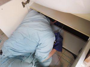 洗面台下から高圧洗浄清掃中