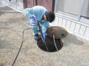 清掃業者の汚水桝高圧洗浄ガン、ジェット噴射作業中