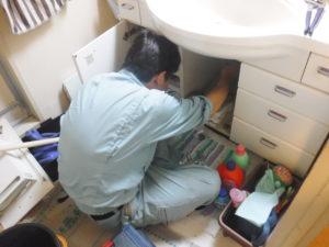 洗面台の下で排水パイプの取り換え作業中