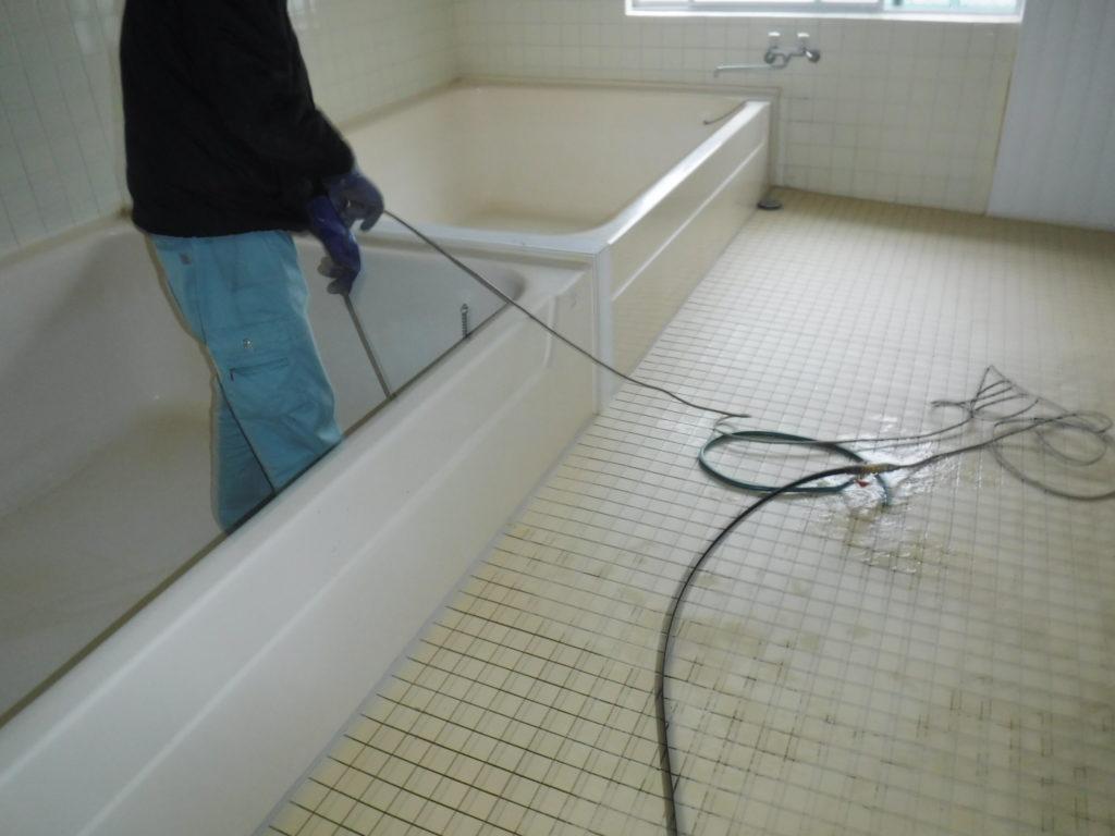 浴場風呂の湯舟排水口から高圧洗浄清掃作業