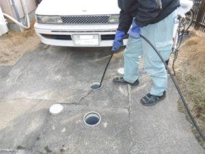家の外でトイレ排水管の高圧洗浄清掃作業