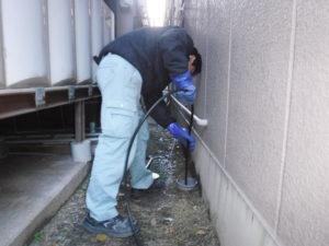 トイレ裏通路での排水管の高圧洗浄清掃作業