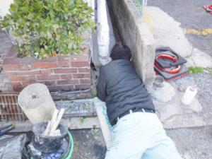 建物と仕切り壁の間で汚水会所の劣化補修作業