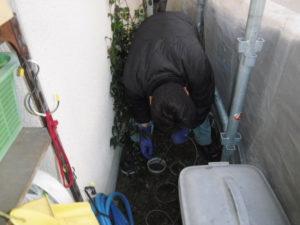 家の外からキッチン雑排水管に向かって高圧洗浄ジェット洗浄清掃作業中