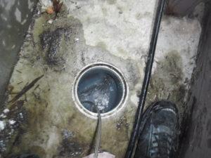 家の裏通路で配管の高圧洗浄作業中